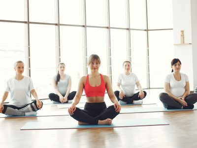Canva - Group of Women Sitting on Blue Yoga Mats